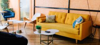 Interieur met gele bank en perzik kleurige muur